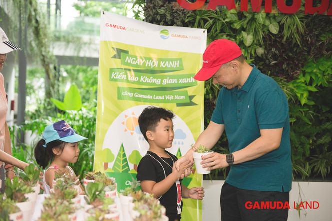 Đại diện Gamuda Land Việt Nam - ông Dennis Ng Teck Yow - tặng chậu cây xanh cho các cư dân nhí tham gia Ngày hội Xanh